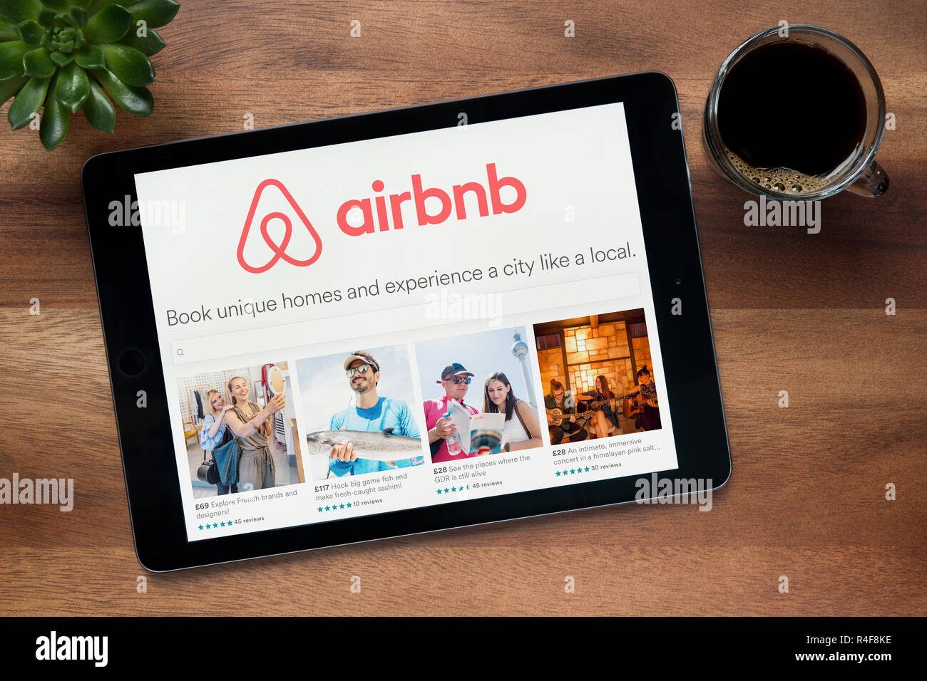 The website of Airbnb is seen on an iPad tablet, on a wooden table along with an espresso coffee and a house plant (Editorial use only). - Stock Image