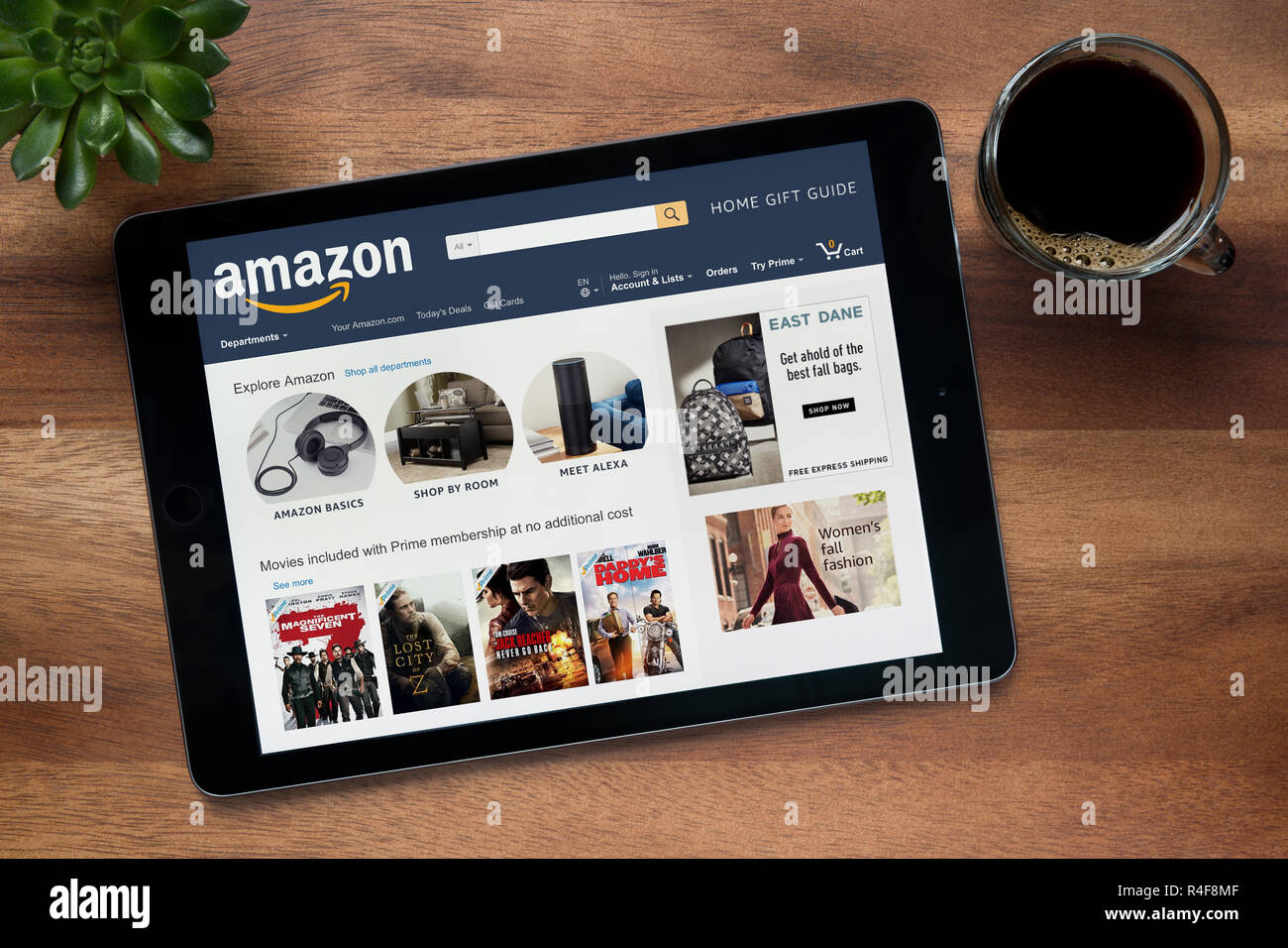 The website of Amazon is seen on an iPad tablet, on a wooden table along with an espresso coffee and a house plant (Editorial use only). - Stock Image