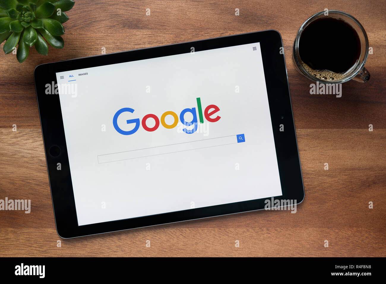 The website of Google is seen on an iPad tablet, on a wooden table along with an espresso coffee and a house plant (Editorial use only). - Stock Image