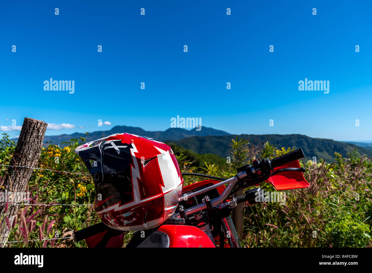 red dirt bike motorcycle and view of Guatemalan mountains landscape - Stock Image