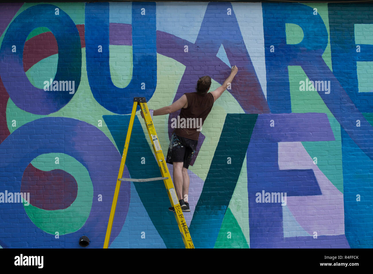 Mural artist just south of Church Street Marketplace. Goes around the country painting murals for various civic groups and cities. - Stock Image