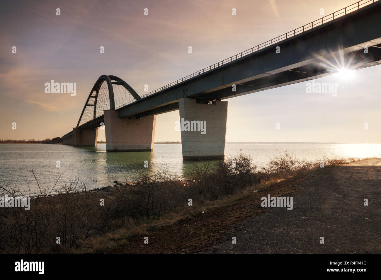 Fehmarn Sound Bridge in sunset (German: Fehmarnsundbrücke), suspension bridge with steel arches connecting the German mainland with the island in the  Stock Photo