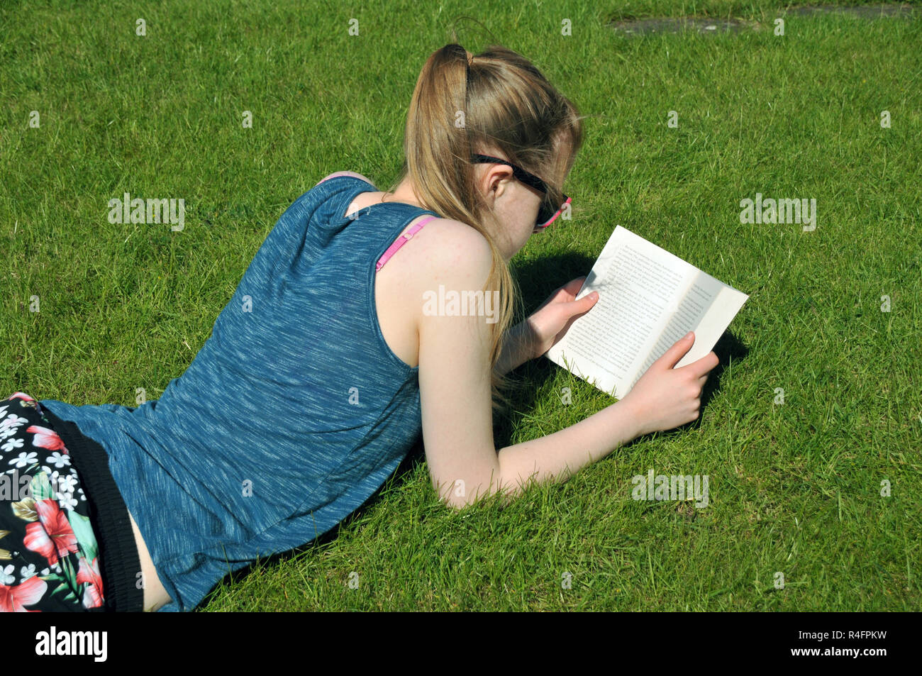 Teenage girl reading a book lying in the garden in summer. Stock Photo