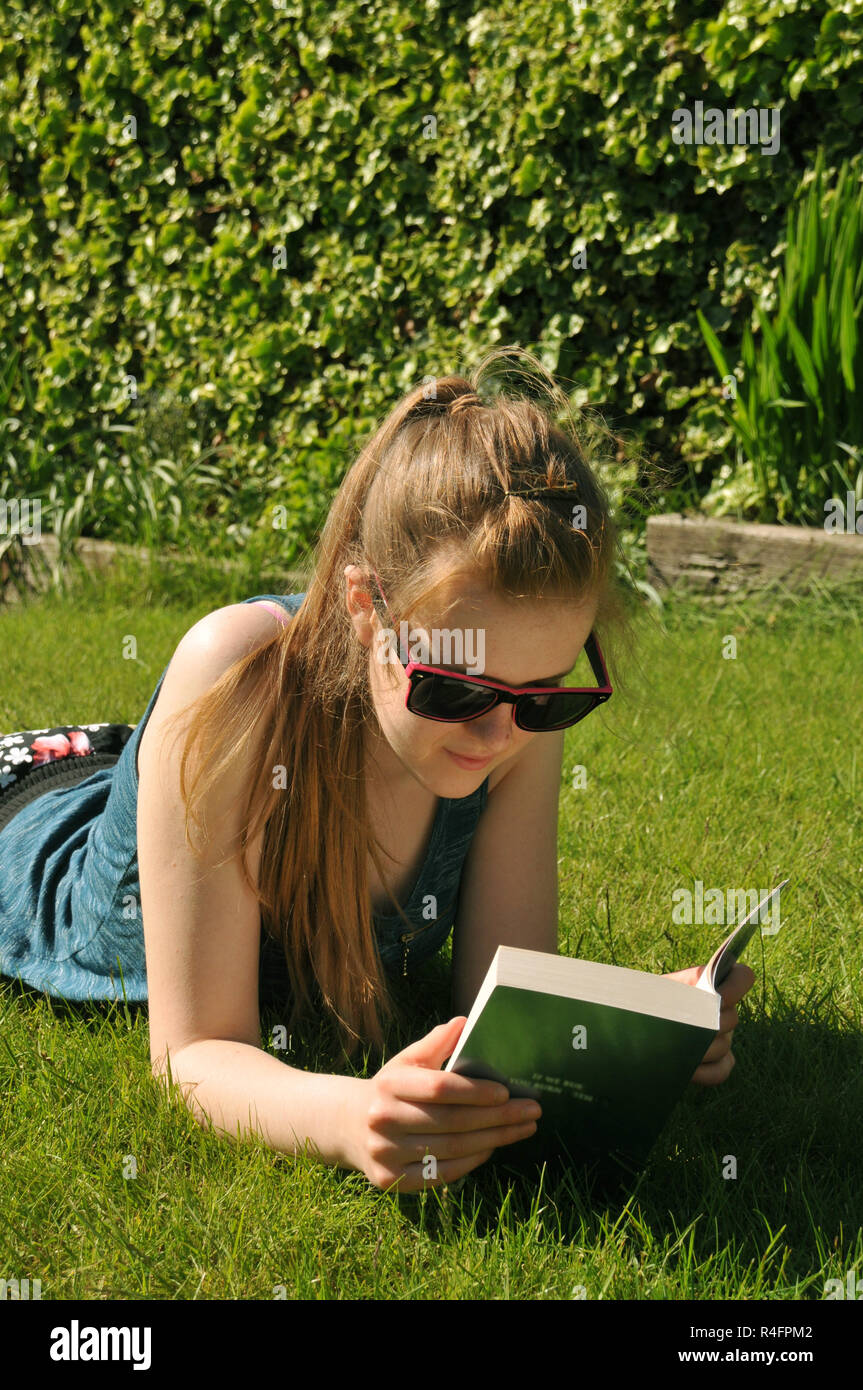 Teenage girl reading a book lying in the garden in summer. - Stock Image