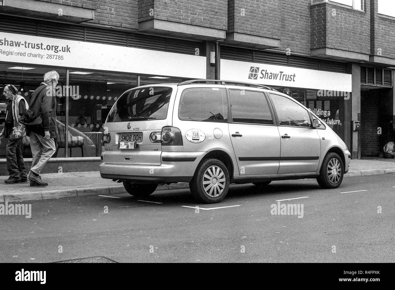 Parked Taxi on a street outside the Shaw Trust in Leicester city centre. shot on a Pentax K1000 slr camera with Ilford 35mm black and white film. - Stock Image