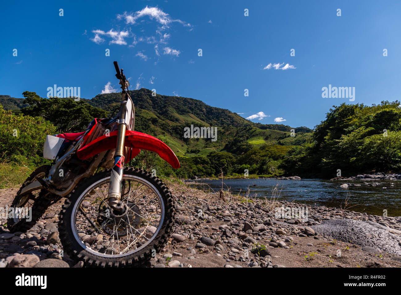 red dirt bike motorcycle and view of Guatemalan mountain and river landscape - Stock Image