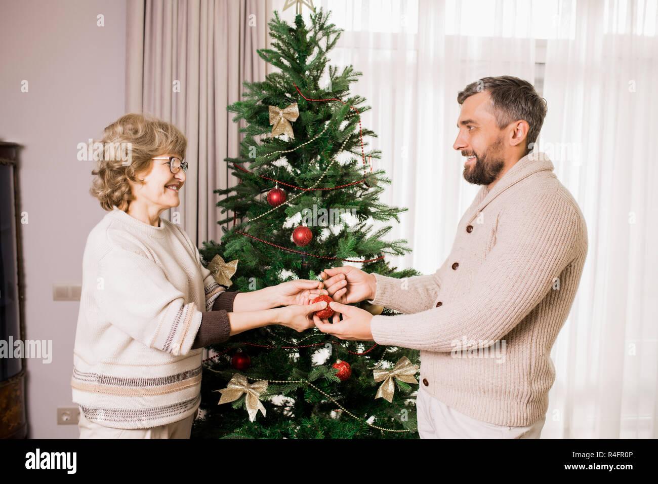 Senior Woman Decorating Tree with Son - Stock Image