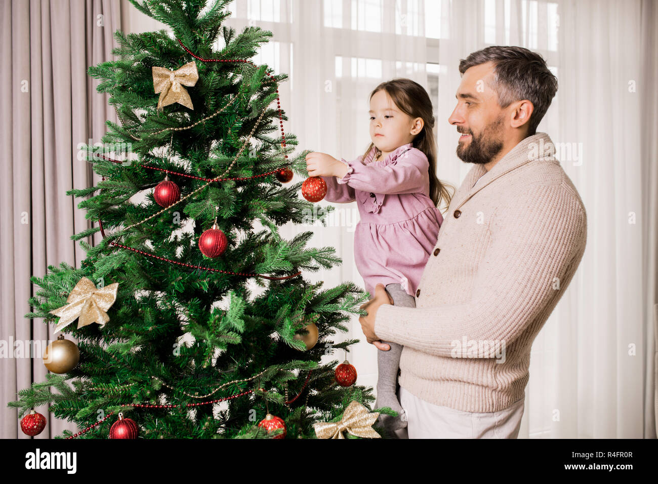 Father and Daughter Decorating Tree - Stock Image