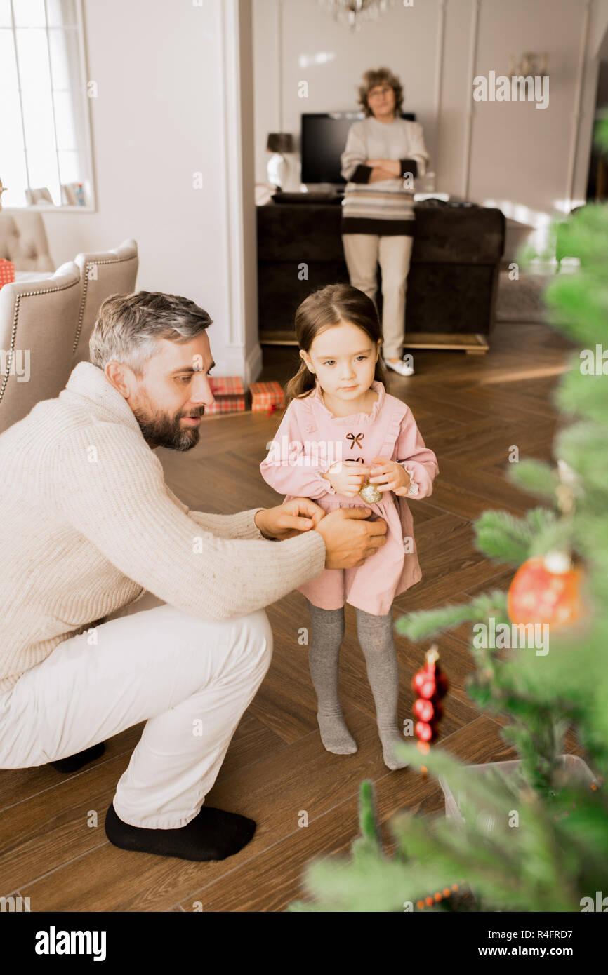 Little Girl Decorating Christmas Tree - Stock Image