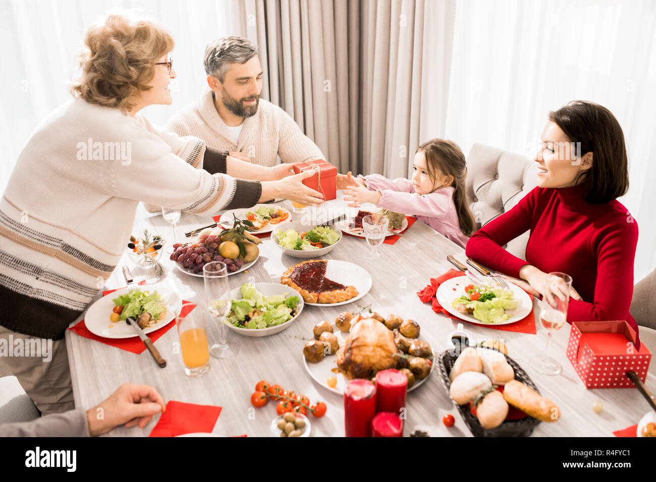 Family Exchanging Presents over Table - Stock Image