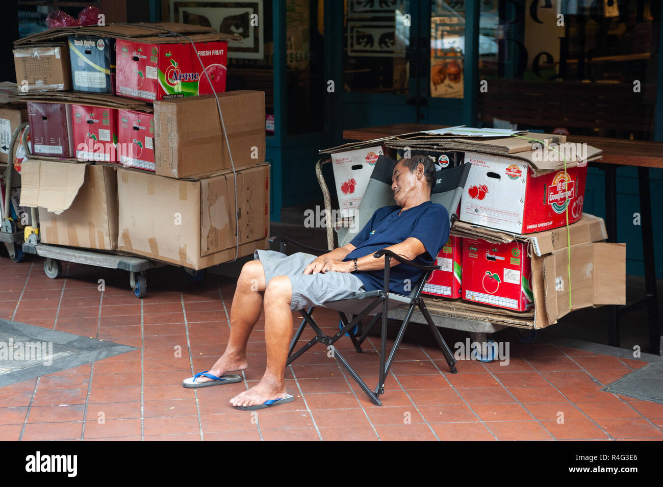 29.07.2018, Singapore, Republic of Singapore, Asia - An elderly man sits on a chair in Singapore's Chinatown district and takes a nap. - Stock Image