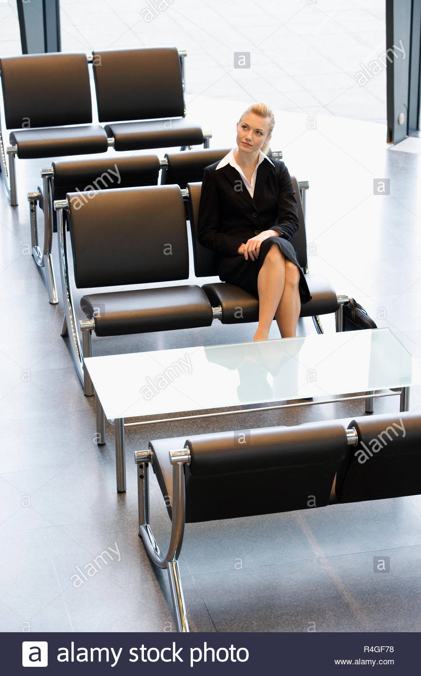 A businesswoman or job candidate sitting in a waiting room - Stock Image