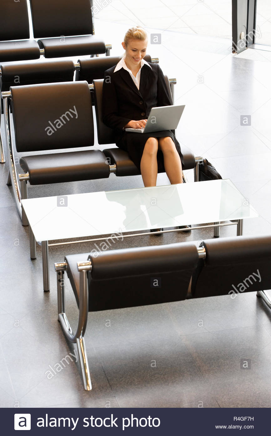 A businesswoman in waiting room, typing on a laptop - Stock Image