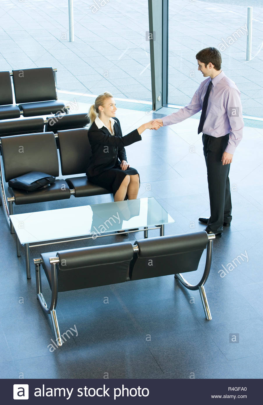 A businessman greeting a client or job candidate - Stock Image