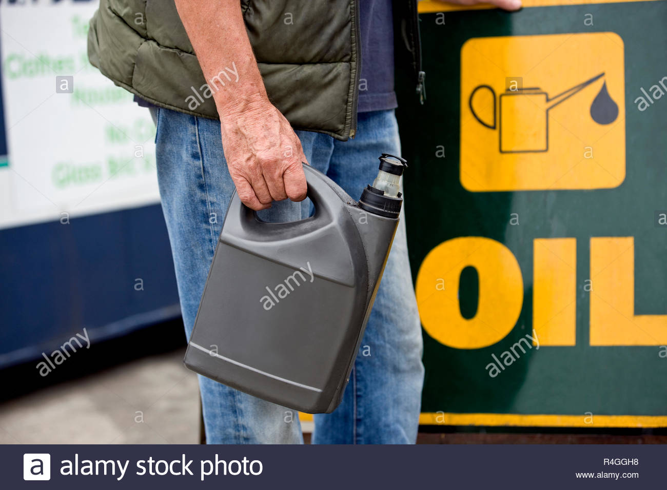 A senior man holding an oil container in a recycling centre, close-up - Stock Image