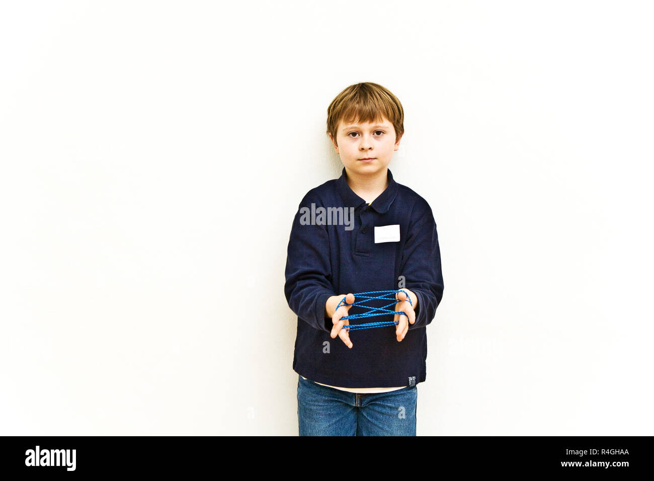 boy is playing a handgame with a band in a museum for modern Art, he enjoys it Stock Photo