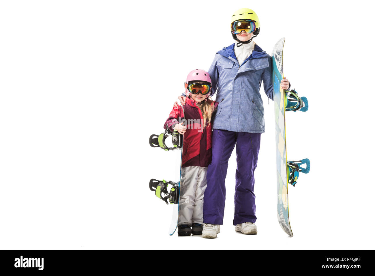 mom and preschooler daughter in ski suits, goggles and helmets with snowboards smiling isolated on white - Stock Image