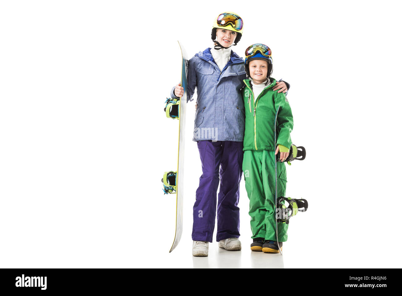 young mom and preteen son in ski suits with snowboards hugging isolated on white - Stock Image