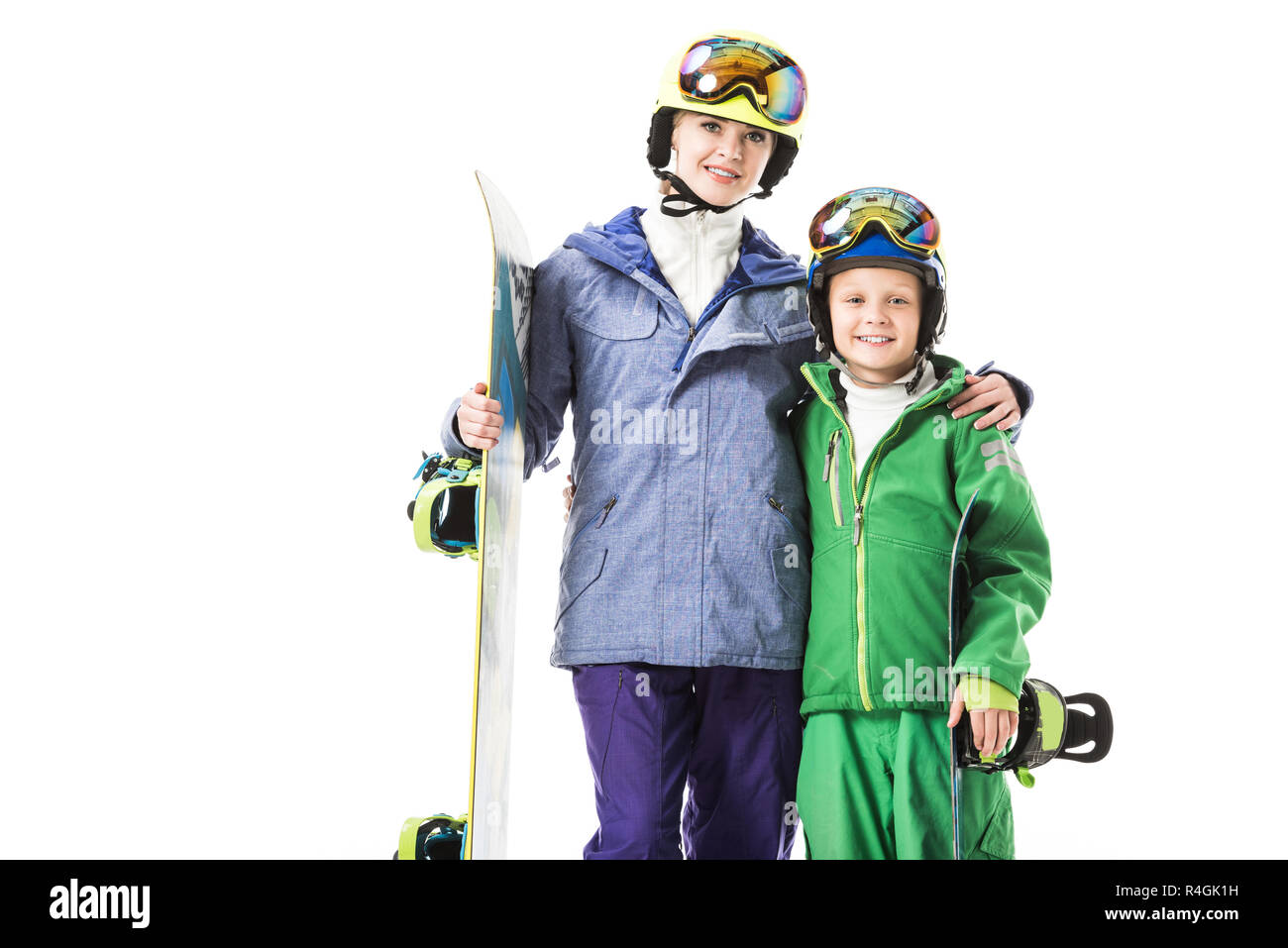 Smiling mom and preteen son in ski suits with snowboards hugging and looking at camera isolated on white - Stock Image