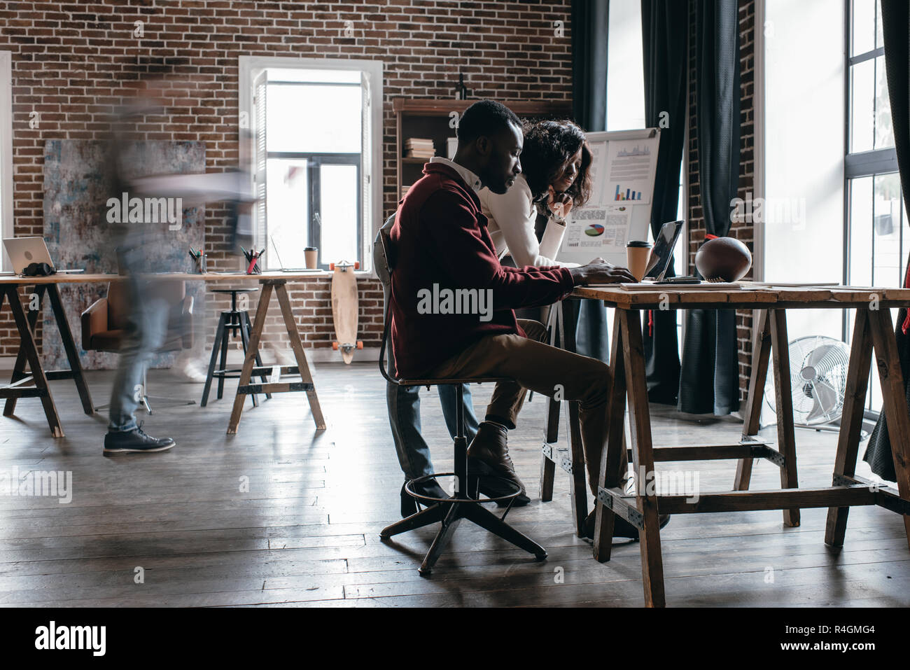 african american couple of casual businesspeople working at desk with colleagues in motion blur in modern loft office - Stock Image
