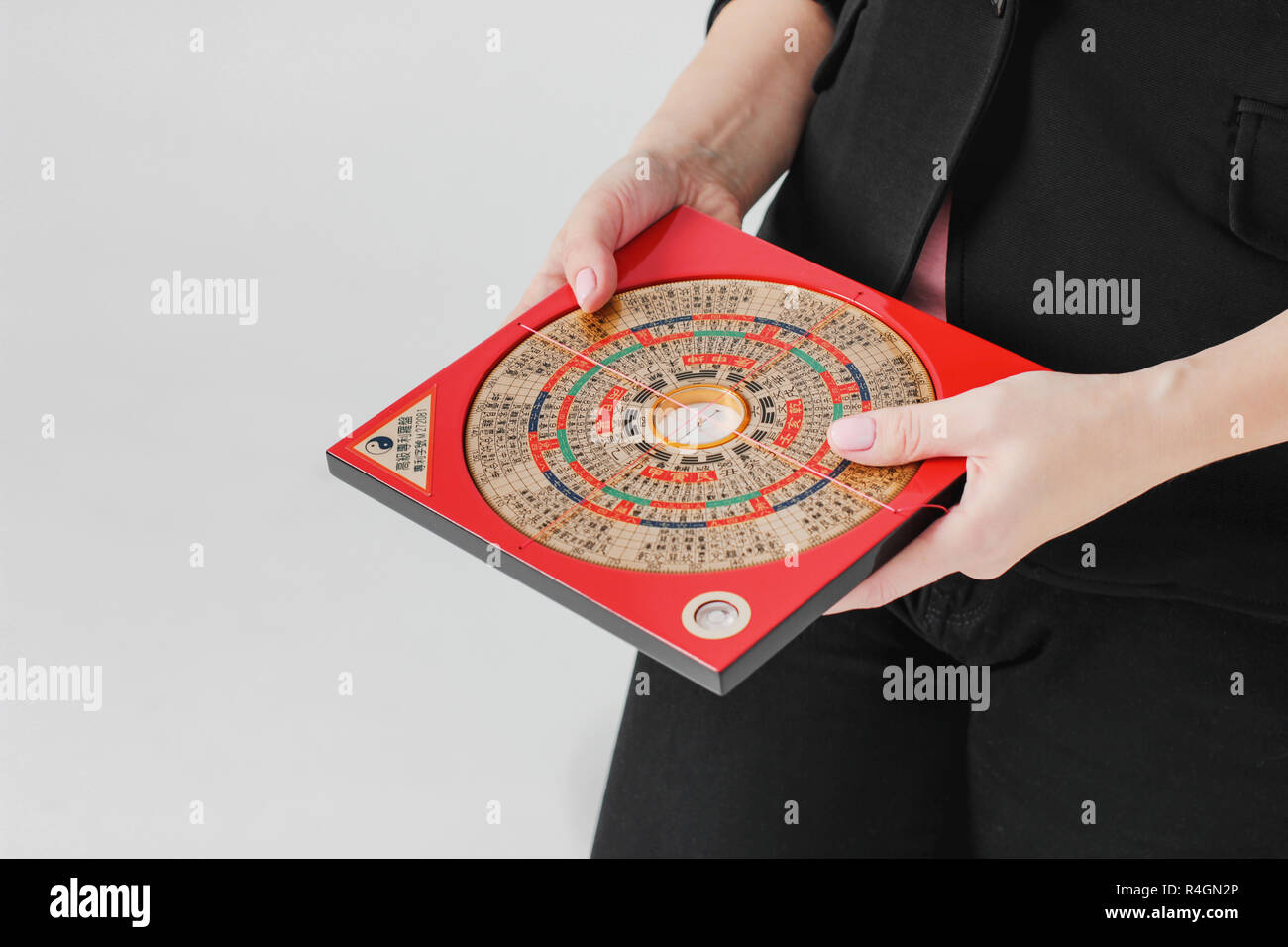 Chinese compass Lopan for Feng Shui technique in female hands isolated - Stock Image