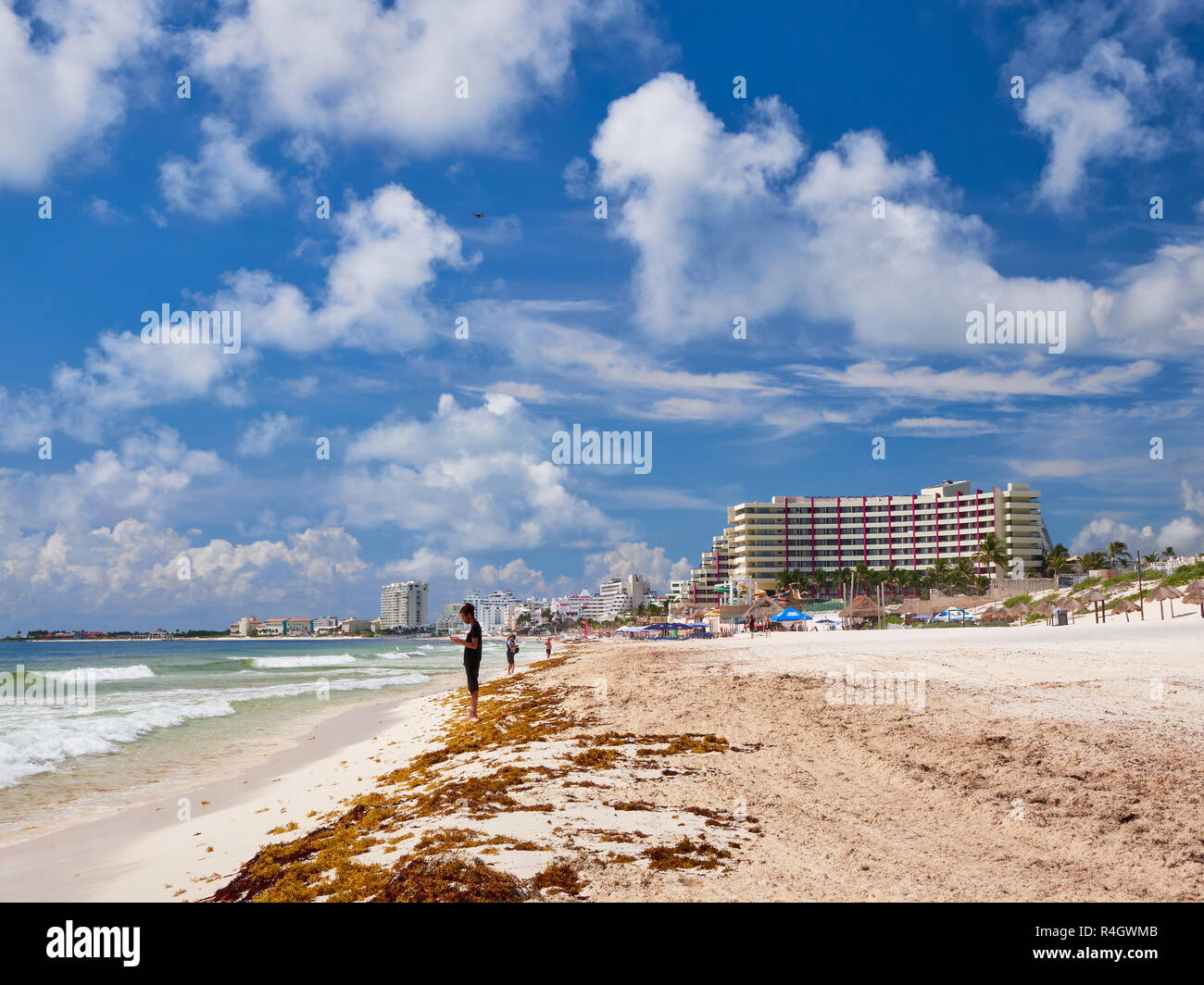 Young boy on Caribbean beach of Playa Delfines have fun with flying drone, Cancun, Mexico - Stock Image