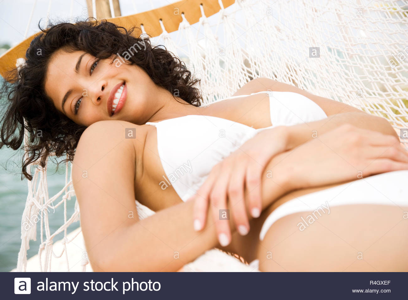 Woman lying in a hammock on a boat in the sun, wearing a white bikini - Stock Image