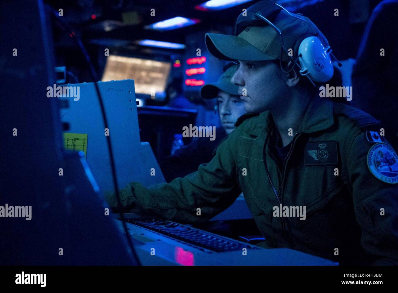 ATLANTIC OCEAN (Sept. 30, 2018) Royal Canadian Navy Lt. Ashley Zen (foreground) and U.S. Navy Operations Specialist 1st Class Jeremy Ables assist in an operations exercise aboard Ticonderoga-class guided-missile cruiser USS Hue City (CG 66). Hue City is currently underway on a regularly scheduled deployment. - Stock Image
