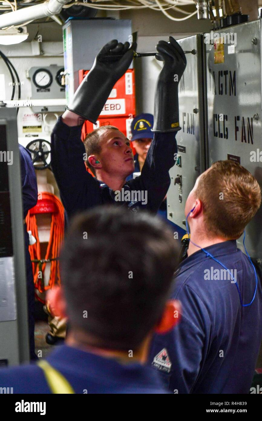 MEDITERRANEAN SEA (Oct. 2, 2018) - Electrician's Mate 3rd Class Francis Murray opens an electrical panel for Sailors to simulate firefighting an electrical fire during engineering training aboard the Arleigh Burke-class guided-missile destroyer USS Ross (DDG 71) in the Mediterranean Sea, Oct. 2, 2018. Ross, forward-deployed to Rota, Spain, is on its seventh patrol in the U.S. 6th Fleet area of operations in support of U.S. national security interests Europe and Africa. - Stock Image