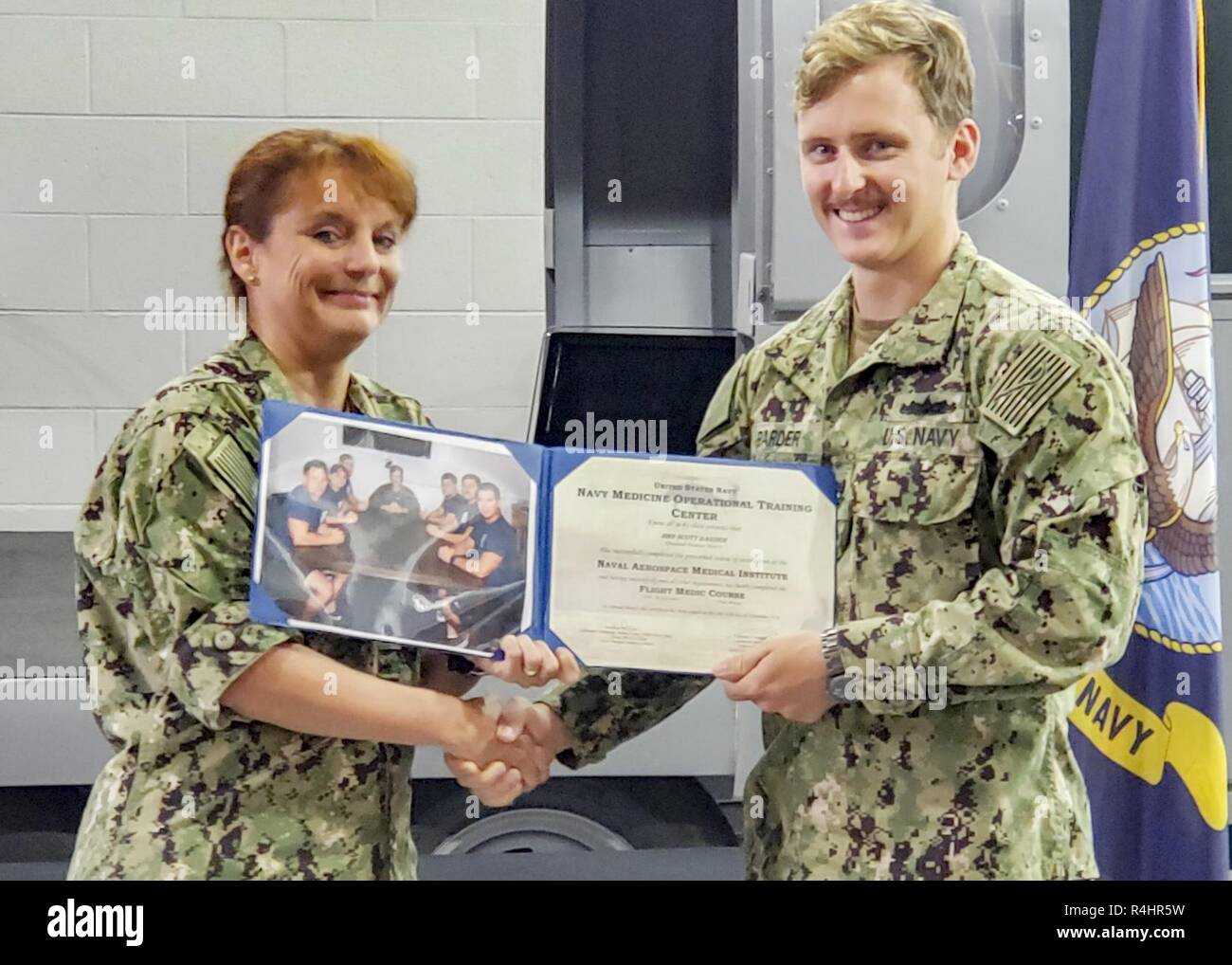 PENSACOLA, Fla. (Sept. 25, 2018) - Cmdr. Malissa Wickersham, left, announces Hospital Corpsman 2nd Class Scott Barder as the honor graduate of the Flight Medic Course (FMC) at Naval Aerospace Medical Institute (NAMI). FMC teaches students the foundations of international trauma life support, pediatric education for prehospital professionals, and advanced cardiovascular life support classes. - Stock Image