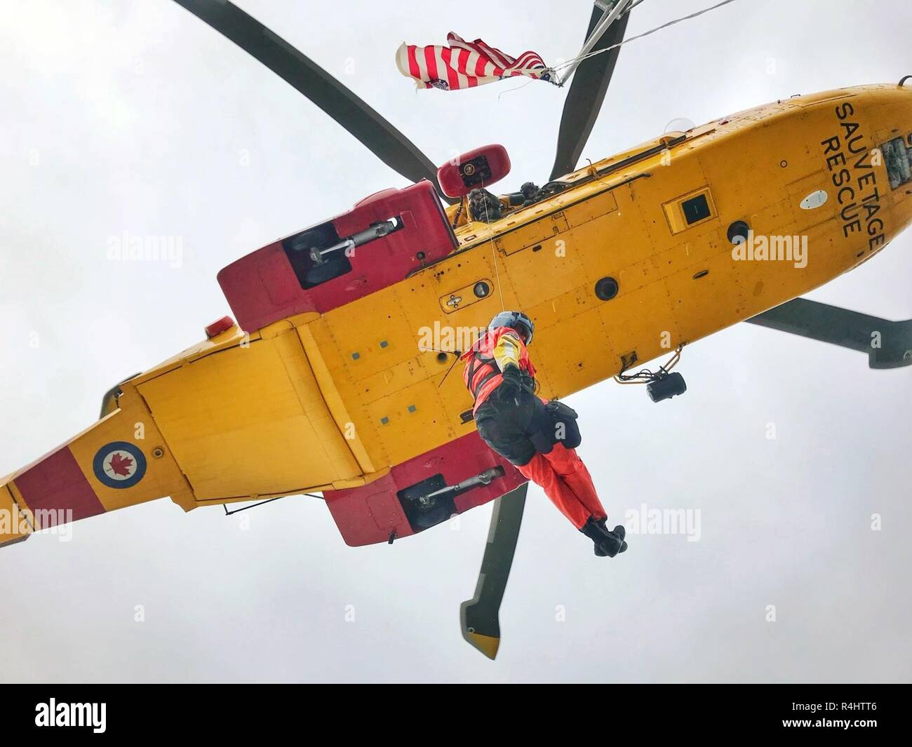 An aviation survival technician from U.S. Coast Guard Air Station/Sector Field Office Port Angeles is suspended by the crew of a Royal Canadian Air Force CH-149 Cormorant helicopter during joint training in the Strait of Juan de Fuca, Wash., Oct. 3, 2018.    The cormorant is one of two primary rotary-wing aircraft used by the RCAF for search and rescue responses. - Stock Image