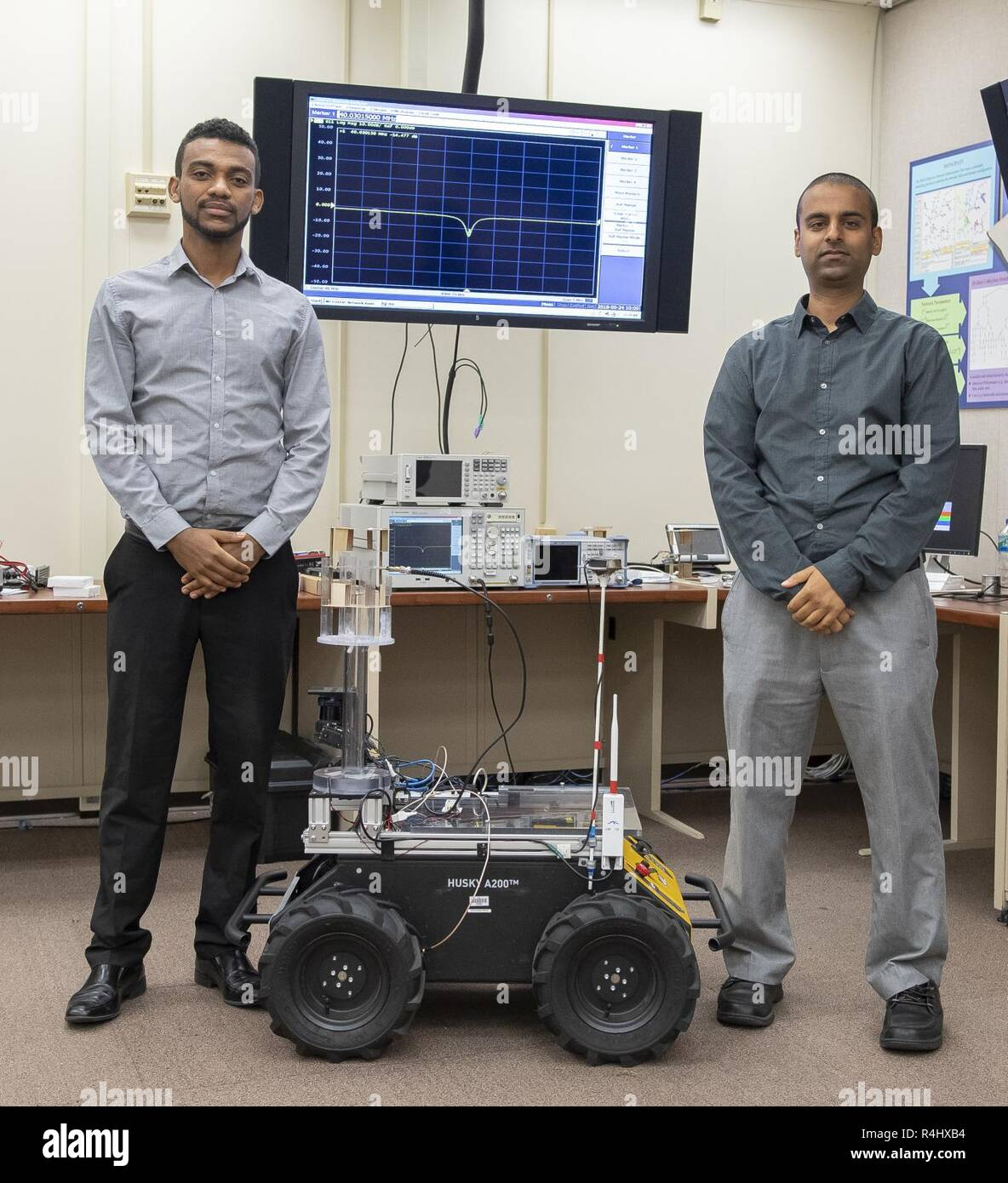 U.S. Army Research Laboratory scientists Dr. Fikadu Dagefu (left) and Gunjan Verma (right) pose with one of the robots used to validate a new algorithm they developed, which enables localization of humans and robots indoors or in areas with many obstacles where GPS signals are likely to be unavailable. - Stock Image