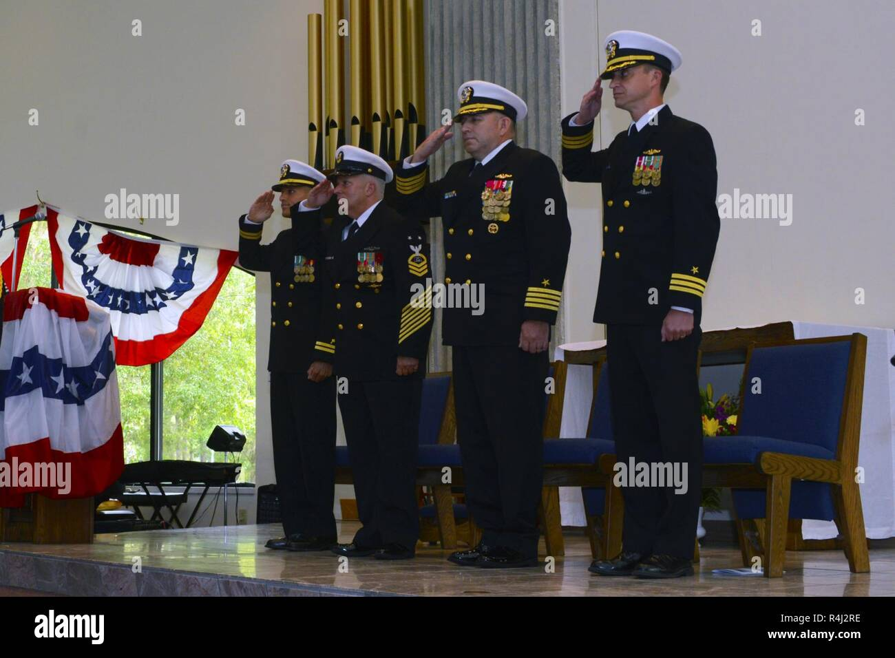 Guests salute during the presentation of colors at Naval Submarine Base Kings Bay, Ga., during a retirement ceremony for Master Chief Culinary Specialist Fernando Colon-Aldecoa. The base is home to five of the Ohio-class ballistic-missile submarines that make up the most survivable leg of the nuclear missile triad. - Stock Image