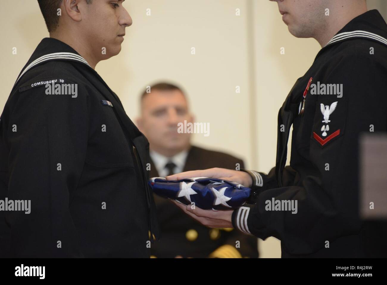 Sailors pass the American flag at a retirement ceremony for Master Chief Culinary Specialist Fernando Colon-Aldecoa held at the Naval Submarine Base Kings Bay, Ga., Chapel. The base is home to five of the Ohio-class ballistic-missile submarines that make up the most survivable leg of the nuclear missile triad. - Stock Image