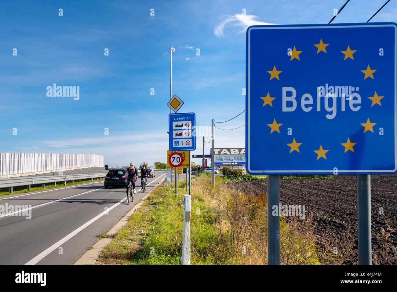 Belgian border sign and cyclists - Stock Image