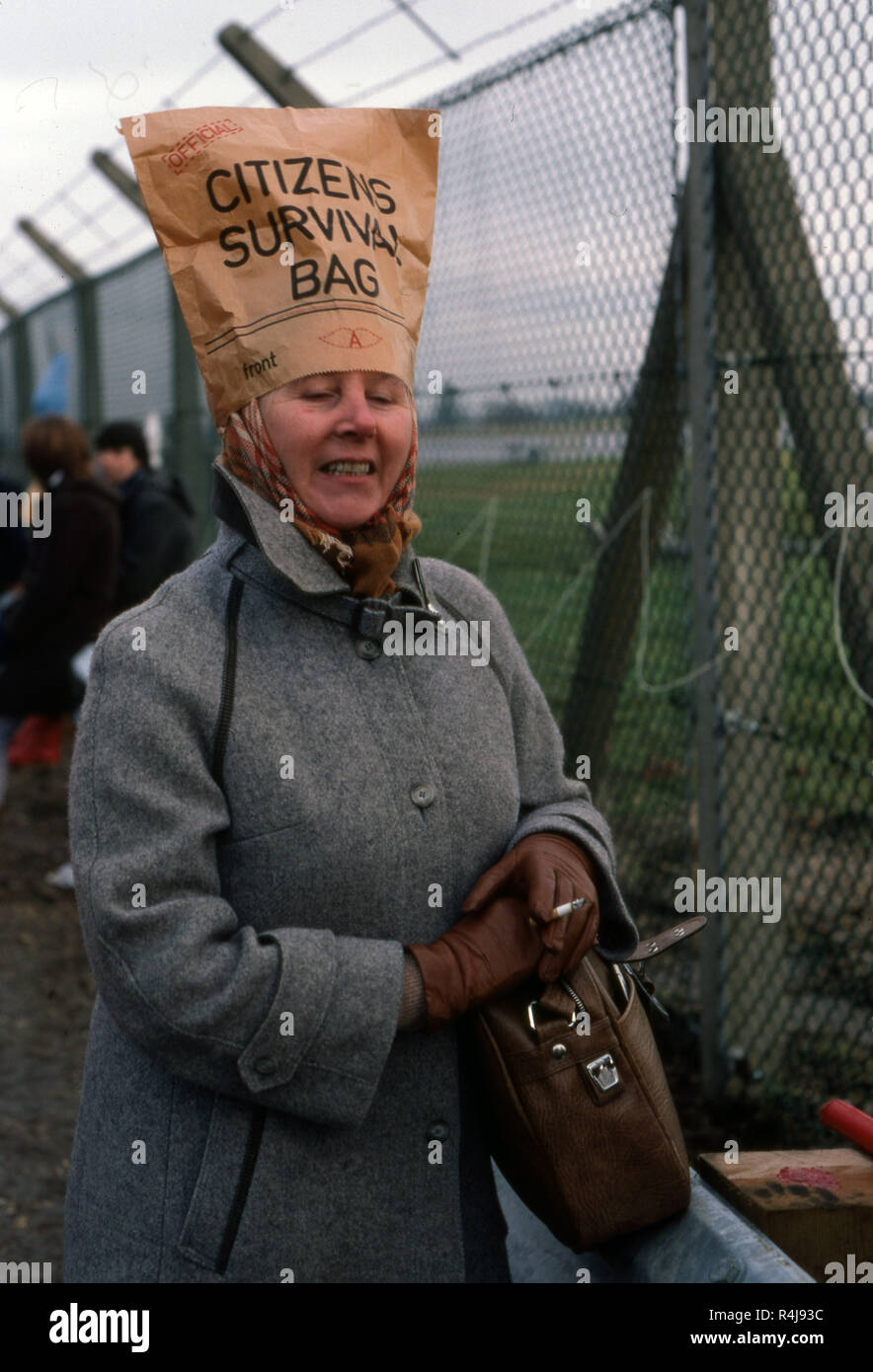 Woman at an Anti-nuclear protest against the replacement of the old trident missile systems at Greenham Common wearing a paper bag on her head entitled Citizens Survival Bag - Stock Image