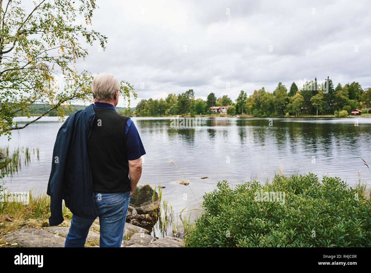 Senior man standing by lake in Falun, Sweden - Stock Image