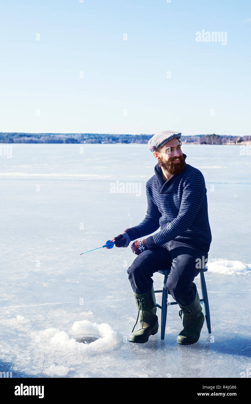 Man fishing on frozen lake in Dalarna, Sweden - Stock Image
