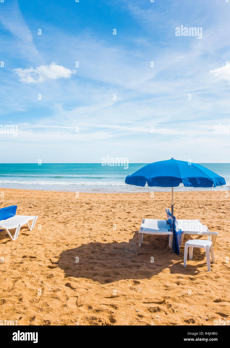 blue umbrellas and sun chairs at deserted beach - Stock Image