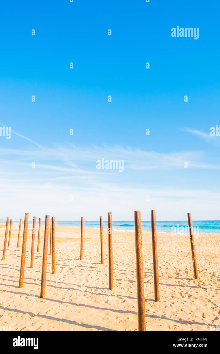 poles at deserted beach - Stock Image