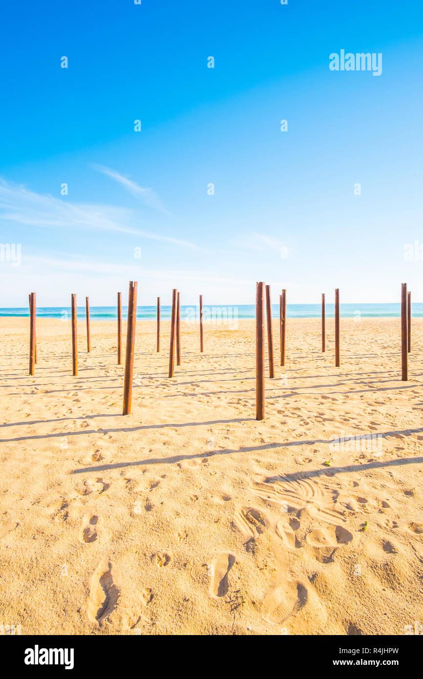 poles at deserted beach, praia grande, armacao de pera, algarve, portugal - Stock Image