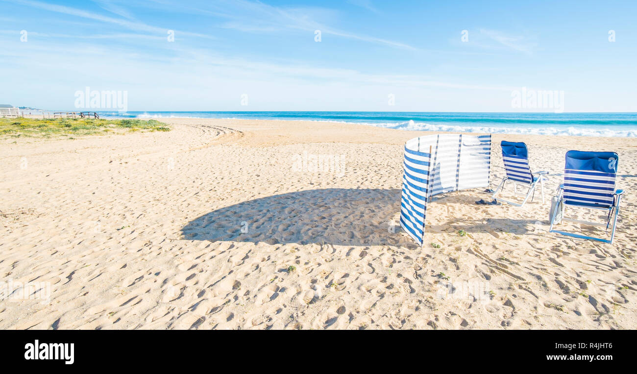 blue and white chairs and wind shelter at deserted beach - Stock Image