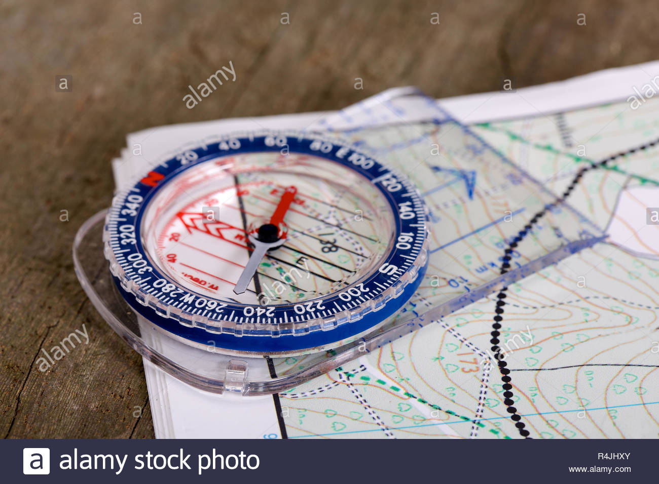Modern plastic compass with scales and rulers, wooden background and detailed hiking map - Stock Image