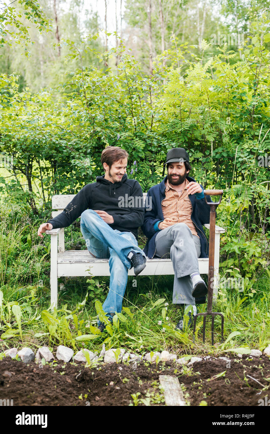 Friends sitting with a gardening fork next to a garden in Dalarna, Sweden - Stock Image