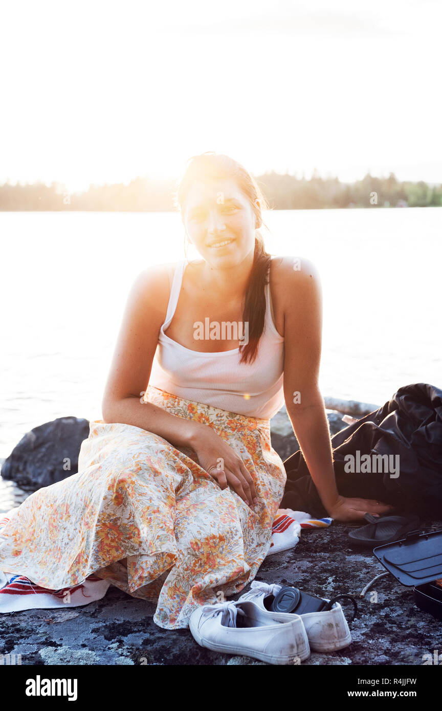 Young woman sitting in front of a lake in Dalarna, Sweden - Stock Image