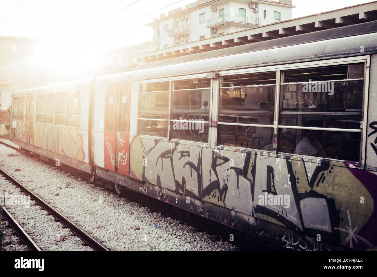 A train with closed doors waiting for passengers at the railway station. Street art and urban culture painted on the tube, Sunlight in background Stock Photo