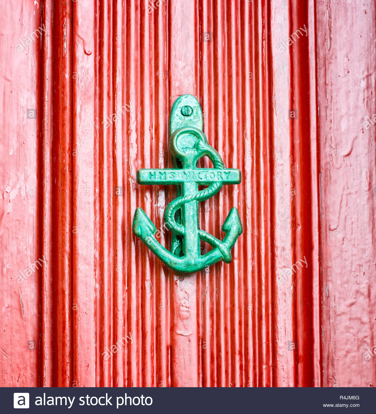 Antique anchor shaped knokcer on a red vintage door - Stock Image