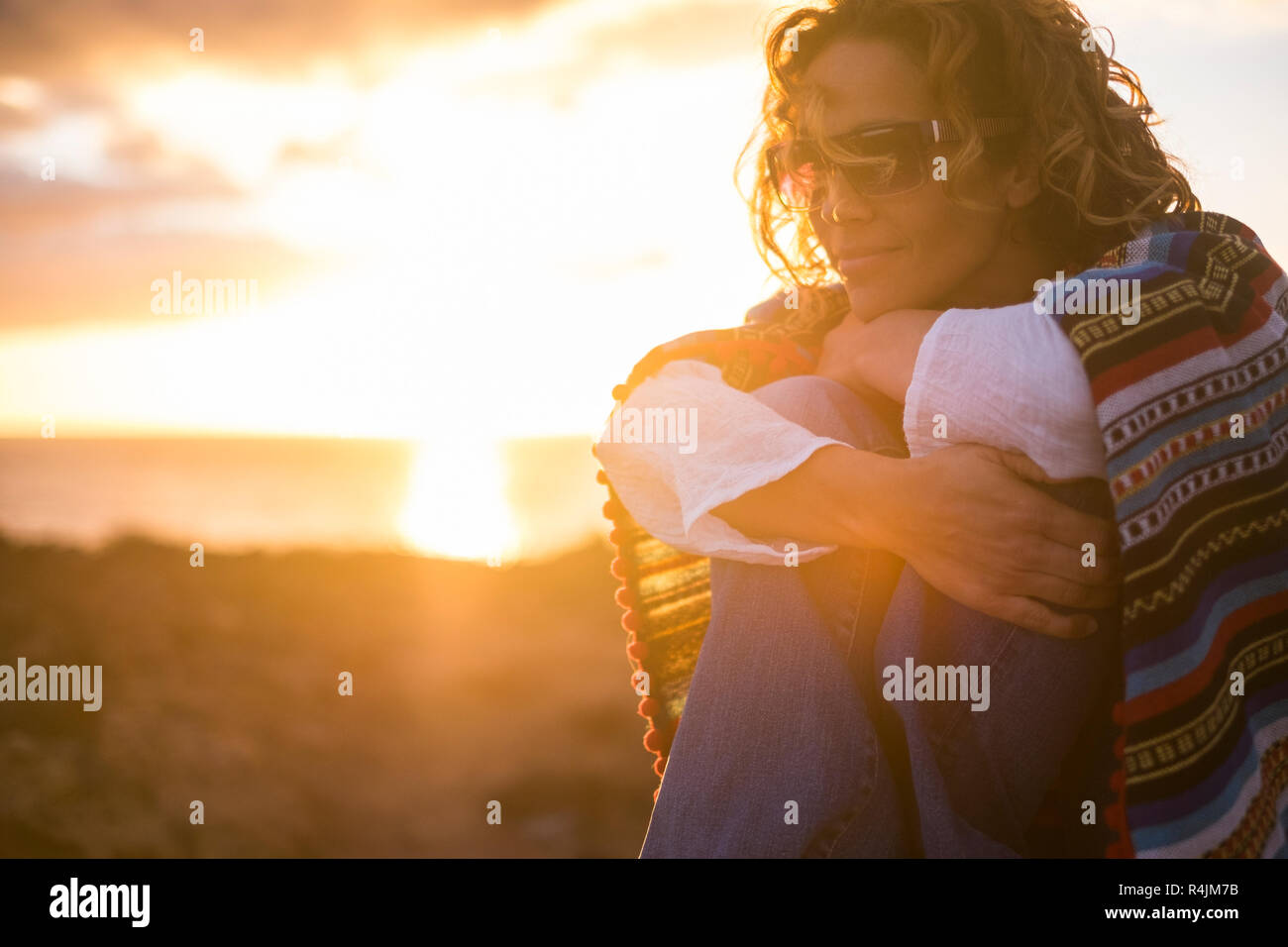 romantic portrait for freedom and peace concept with beautiful middle age caucasian lady stay sit down with mexican poncho and golden light from sunse - Stock Image