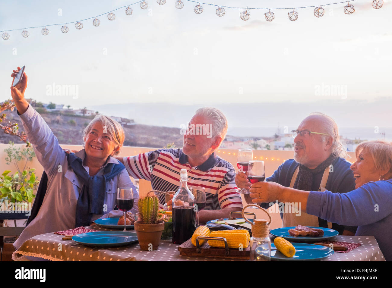 four adult matures people men and women have fun together eating and drinking on the terrace with great view on the city - the lady take a selfie pict - Stock Image