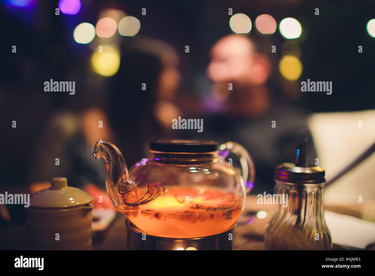 Teapot and glass cups with tea against wooden background. against the background of the restaurant in the evening. - Stock Image